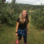 Girl hiking in greenery and apple picking