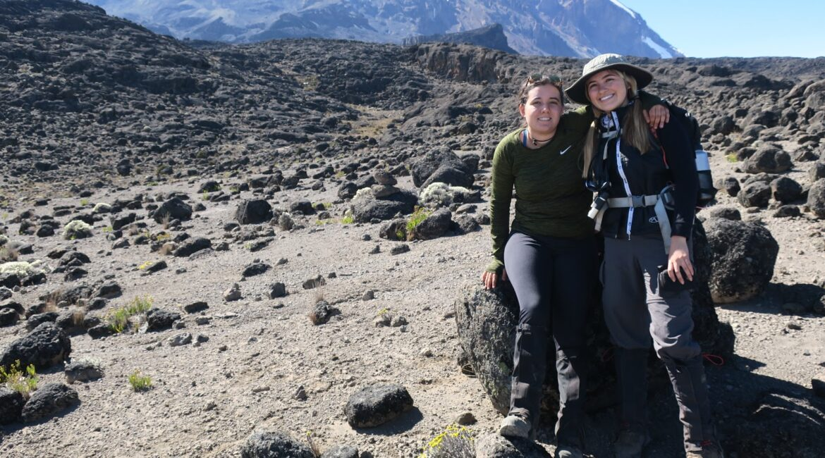 Two women sitting on a rock, Kilimanjaro in the background.