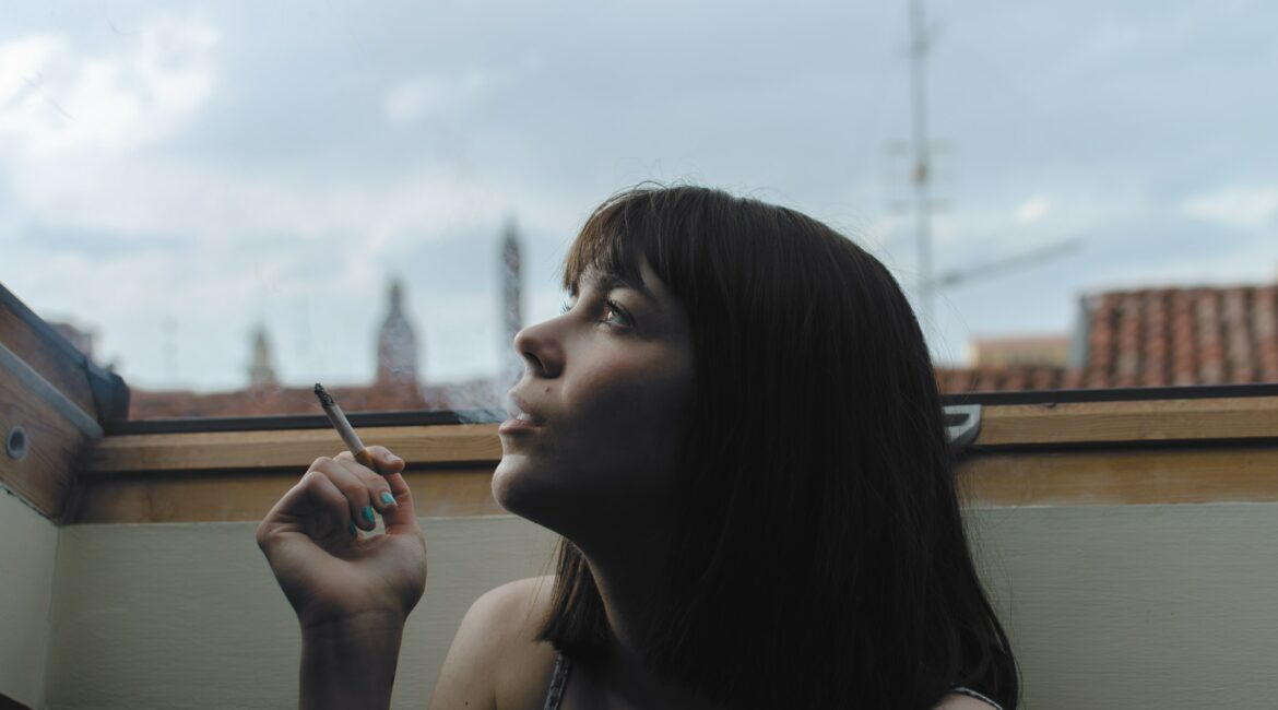 Girl smoking and looking up, side profile