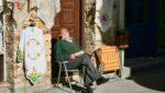man asleep on cobblestone street