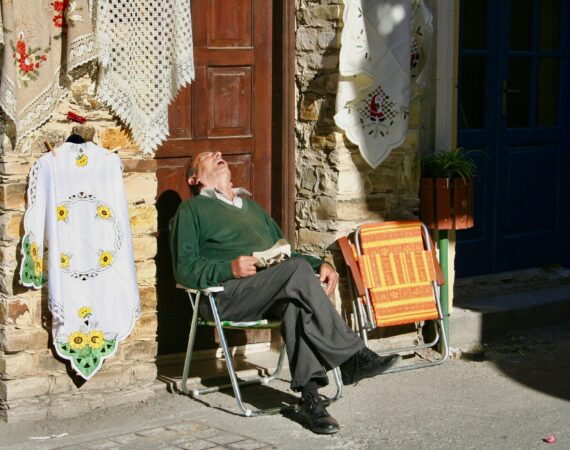 man asleep on cobblestone street