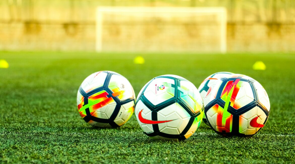 Soccer balls on green field